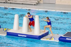 People running through an Aquaglide inflatable barricade.