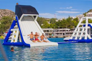 A group of men are sliding down a Freefall-supreme waterslide.