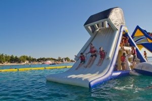 A man and two children are sliding down a Freefall-supreme waterslide.